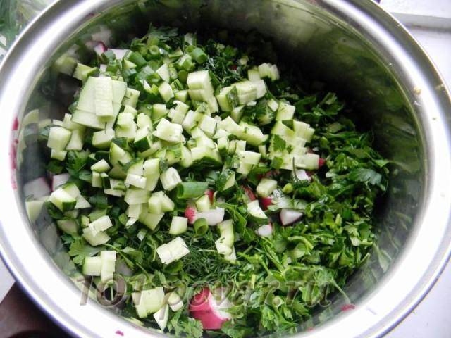 Мелко нарезаем редиску, огурцы и зелень и отправляем все это к картофелю и яйцам