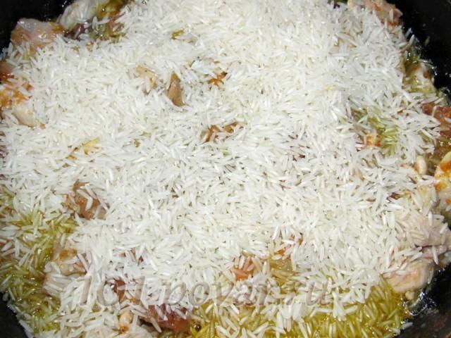 К обжаренным мясу и овощам добавить сухой рис, перемешать и держать на огне не более 1 минуты