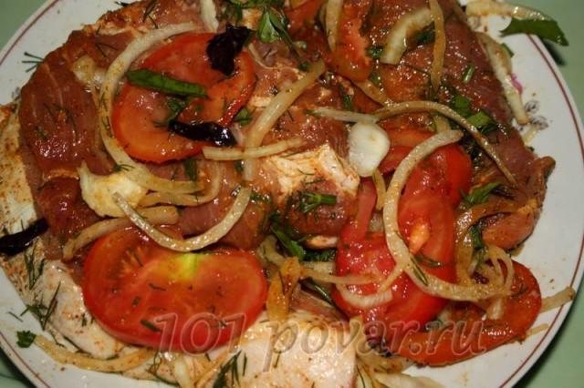 Кусочки мяса, чередуя с луком помидорами и зеленью, выложить в удобную емкость, слегка помять руками, чтобы овощи дали сок