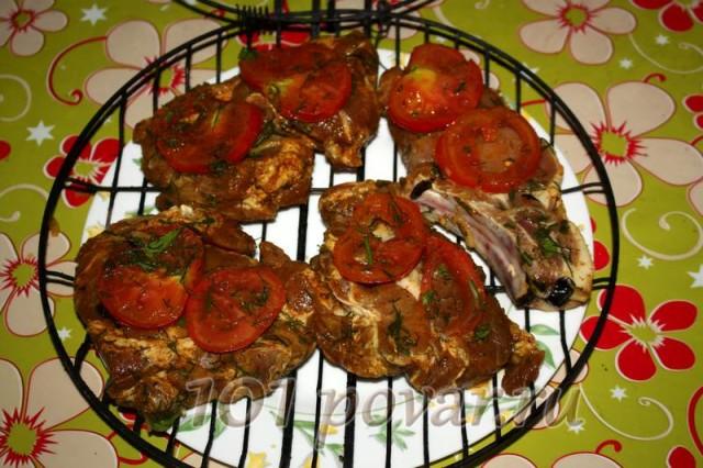 Промаринованное мясо выложить на решетку, можно вместе с помидорами