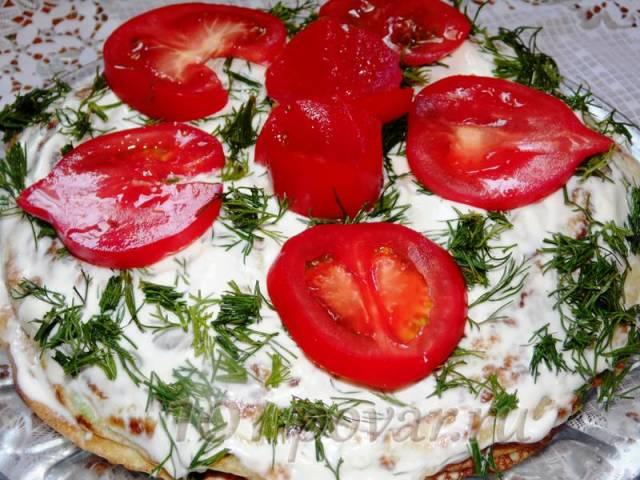 Накрываем вторым блином и все повторяем, пока не закончатся блины. Верх торта смазываем майонезом и украшаем помидорами.
