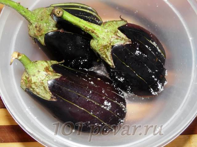 Баклажаны нарезаем не до конца на шайбочки толщиной в 1 см, солим между разрезами, чтобы соль попала на внутреннюю белую часть овоща и помещаем их в миску