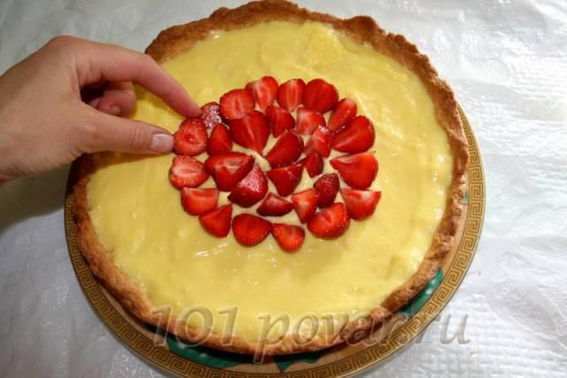 На охлажденный пирог ложкой выкладываем крем и распределяем по всей поверхности. Затем берем клубнику и выкладываем ее по кругу, начиная с центра, до бортиков.