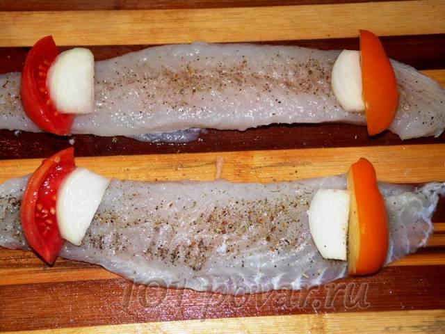С двух сторон выкладываем на концы филе дольки помидор разного цвета и луковые дольки