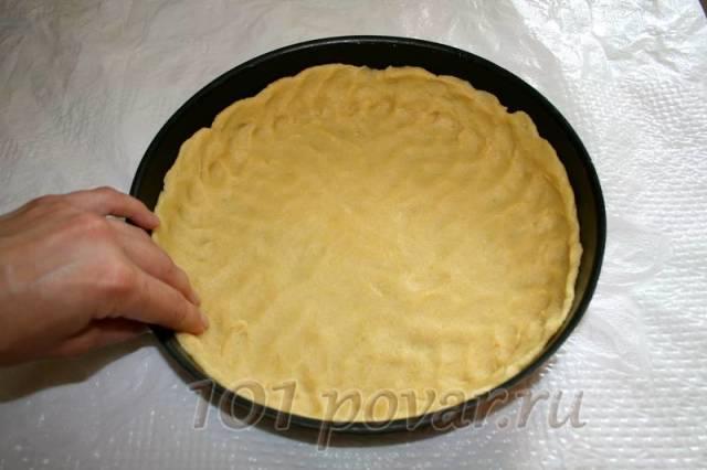 Круглую форму для выпечки смажьте маслом, положите в нее охлажденное тесто и руками распределите его по всей форме, сделав бортики