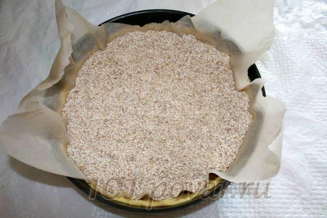 На тесто выложите лист пергамента и высыпьте на него крупу по высоте бортиков. Это нужно для того, чтобы при выпекании бортики держали форму.